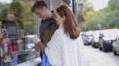 produto : Young couple talking and walking down the street. They both stop to look at some products in a shop window.