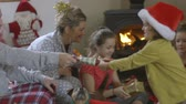 A happy family laugh and smile as they enjoy Christmas morning together. The little boy and his dad are pulling a cracker togeher as his sisters and mother look from behind.