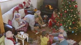 gratitude : A happy family gather in the living room together while they open their Christmas presents. The grandparents are watching their children and grandchildren together. The little boy is pulling a Christmas cracker with his uncle. Stock Footage