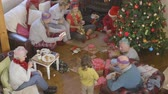 receber : A happy family gather in the living room together while they open their Christmas presents. The grandparents are watching their children and grandchildren together.