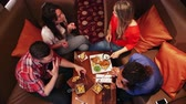 diretamente acima : Aerial view of a group of friends eating at a restaurant. They are talking and sharing their food.
