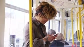 amarelo : Woman standing on a train using a smart phone to text. Stock Footage