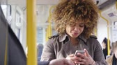 byt : Woman travelling on a train. She is using a smart phone and other people can be seen using technology around her.
