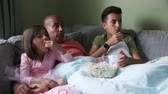 corner : Father at home with his children. They are curled up on the sofa watching a film with a bowl of popcorn.