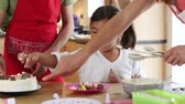 glacé : Little girl decorating a cake at home with her brother and her sister. They are putting icing and sweets on it.
