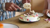 slices : Family at home celebrating a birthday. The father is cutting the cake into slices and putting them on to plates. Stock Footage