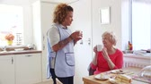 diário : Senior woman talking to her home caregiver over a cup of tea and some cake.