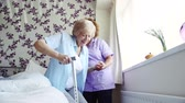 zdravotní sestra : Home caregiver assisting a senior woman as she gets up from sitting on the bed. Dostupné videozáznamy
