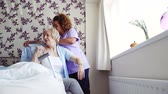 zdravotní sestra : Home caregiver helping a senior woman get dressed in the bedroom of her home.