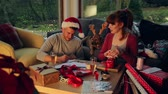 hat : Young couple at home with their pet dog at Christmas time. They are writing out cards and wrapping presents together.