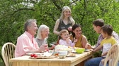 pimentas : Family are sitting outdoors in summer to have a picnic meal.