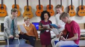 rehearsal : Teenage male students are in a music lesson in high school. They are discussing sheet music with their female teacher. Stock Footage