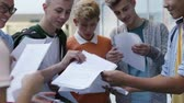 Group of teenage students are getting their exam results. They are comparing grades happily. Dostupné videozáznamy