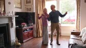 женат : Slowmo shot of senior couple dancing together in the living room of their home.