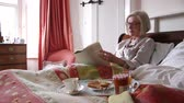 jornal : Senior woman is content in bed in the morning. She is having her breakfast and reading the paper.