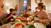 готов к употреблению : Family are sitting at the dining table enjoying christmas dinner together.