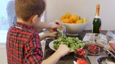 turcja : Two brothers are helping to prepare the Christmas dinner. They are placing brussel sprouts and cranberries on plates in the kitchen of their home.