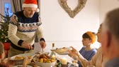 esculpida : Mature man is serving his family the turkey that he has carved at christmas dinner.