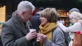 contato : Mature couple are drinking hot drinks in a town christmas market.