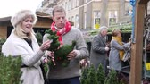 зелень : Mature couple are enjoying buying christmas decorations in the town christmas market.