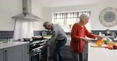 pimentas : Senior couple are preparing food in the kitchen of their home. Vídeos
