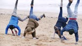 piada : A group of teenagers have fun on a winter beach doing handstands.