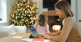 lareira : A mother is working on her laptop from home at christmas time. She is watching her daughter dance in front of the christmas tree. Stock Footage