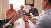 banquete : Men are eating at a dinner party. One man passes his plate for someone to put a piece of food on it.