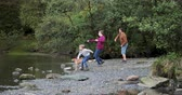 seixo : Two boys are having a pebble throwing competition with their father at a lake they have found while hiking.