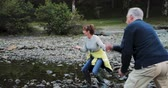 simplicidade : Senior couple are skimming stones together on a lake while out hiking the Lake District. Stock Footage