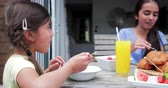 łyżka : Side angle view of a little girl eating cornflakes outside while on holiday with her family.