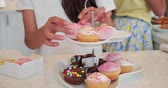 de cor : Little girl sorting through cupcakes on the cake stand. Vídeos