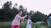 домик : Slow motion, low angle view shot of sisters, moving and playing with bubble wands, creating bubbles.
