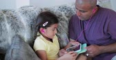 piada : Father helping his daughter and spending quality time together on a digital tablet.