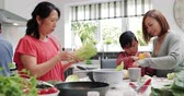 variação : Three generation family are all helping to make a stir fry together at home.