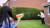 front or back yard : Little girl is having a water fight in the garden with her Dad using water pistols.