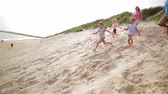 nagymama : Slow motion shot of a family racing down a sand dune while on holiday. Stock mozgókép