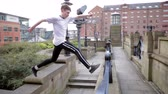 outdoor pursuit : Freerunner is jumping over walls in Newcastle city centre.