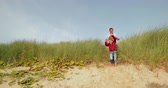 Slow motion of a family walking down to the sea front from the sand dunes. Dostupné videozáznamy