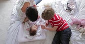 months : Little boy and his mother are being playful with the baby after changing her nappy on the bed.