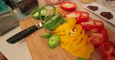 slices : Close up shot of slices of bell pepper on a chopping board in a home kitchen.