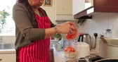 curry : Close up shot of a mature woman blending vegetables in a food processor while cooking a curry at home.
