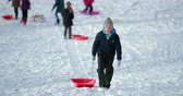 tobogganing : Little boy and his friends are walking up a big hill in the snow to have a sled race.