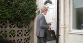 rotina : Side view of a young businessman walking out of his house, locking the door and then leaving. Stock Footage