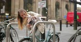 fastening : Young businesswoman locking up her bicycle at the rack before she goes into work.