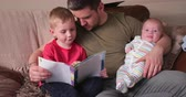 workbook : Mid-adult father is holding his newborn baby boy in his arm and reading through a book with his son. They all are sitting on the sofa in the living room. Stock Footage