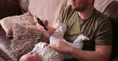 портативный : Father resting baby boy on his lap while he sleeps and holds his phone in his other hand. Стоковые видеозаписи