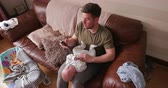gleichgewicht : Mid-adult father sitting on the sofa in the living room while comforting his newborn baby and using his mobile phone.