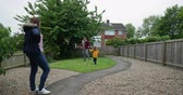 front or back yard : Mother standing in their front or back yard watching her husband and their son use their imagination to play fight on the grass with a toy sword and shield. Stock Footage