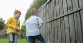 チョコレート : Slow motion shot of two little boys finding chocolate easter eggs which have been hidden in a back garden. 動画素材